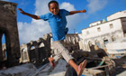 A Somali boy jumps between old fishing boats