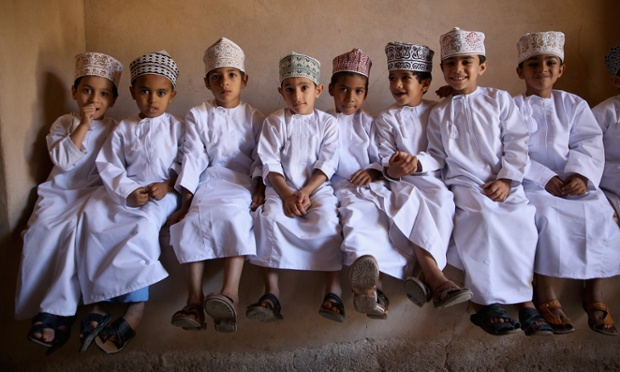 Young Omani children wait in the shade before greeting Prince Charles and Camilla, Duchess of Cornwall as they visit Nizwa Fort on the eighth day of a tour of the Middle East in Nizwa, Oman.