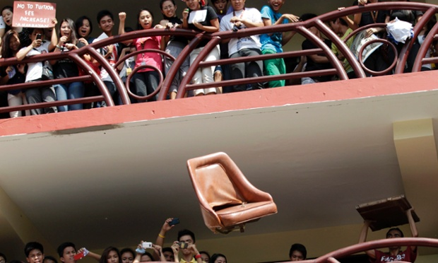 Filipino activists throw a chair from the balcony of a building during a symbolic protest following an apparent suicide by a college student at the Polytechnic University of the Philippines (PUP) in Manila.