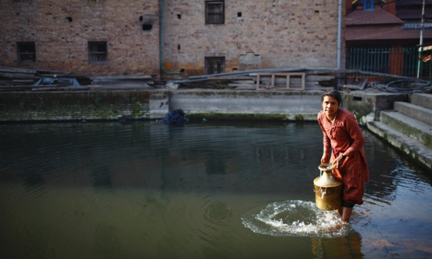 A woman fills a container with water from a pond at the ancient city of Bhaktapur near Nepal's capital Kathmandu.