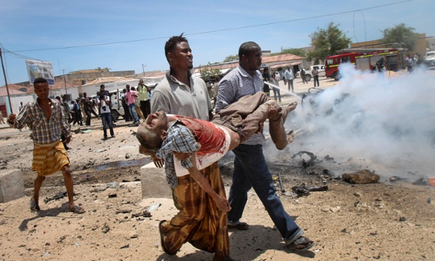 Here Somali men carry a seriously wounded man after the bomb blast which was close to government buildings. At least seven people have been killed.