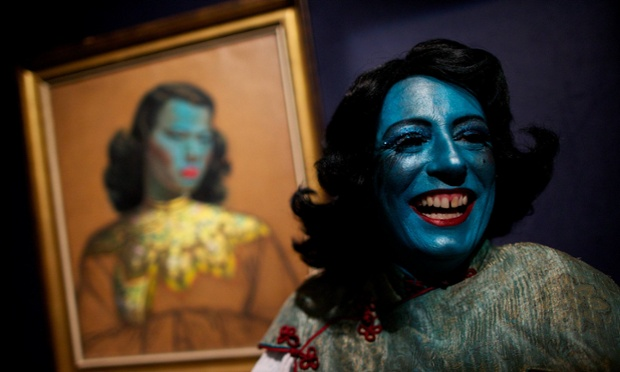 Cabaret singer Tricity Vogue dressed as the blue lady a character inspired by the painting Chinese Girl by artist Vladimir Tretchikoff by the painting at Bonhams auction house in London. It's estimated to make £300,000 to £500,000.