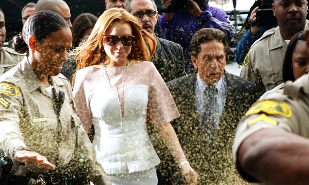Actress Lindsay Lohan is showered with gold glitter, as she walks into court with her attorney Mark Heller, in Los Angeles. Lohan is charged with three misdemeanor counts stemming from a crash on Pacific Coast Highway.