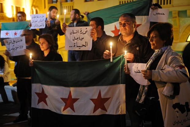 Lebanese activists light candles as they hold Syrian revolutionary flags during a rally to mark the second anniversary of the Syrian revolution against the regime of President Bashar al-Assad in downtown Beirut, Lebanon. Photograph: Wael Hamzeh/EPA