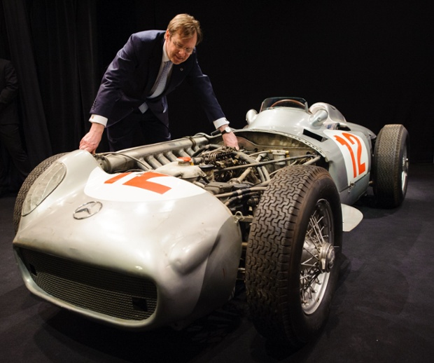 Chairman of Bonhams auction house Robert Brooks examines the 1954 2.5 litre Mercedes-Benz W196 Formula 1 Grand-Prix single-seater driven by Juan Manuel Fangio, at a photocall at Bonhams, in central London, United Kingdom. The car, which Fangio drove to victory in the German and Swiss Grand Prix, will be auctioned at the 2013 Goodwood Festival of Speed. Photograph: Dominic Lipinski/PA