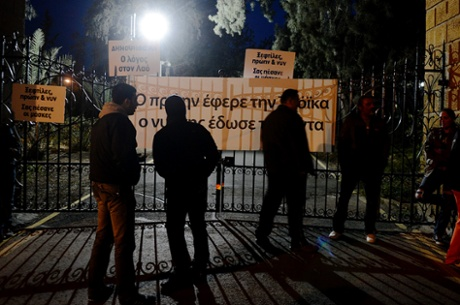 Protestors are seen next to banners during the rally against ratification of a one-off tax in front of the gate of Presidential Palace in Nicosia, Cyprus, 18 march 2013.