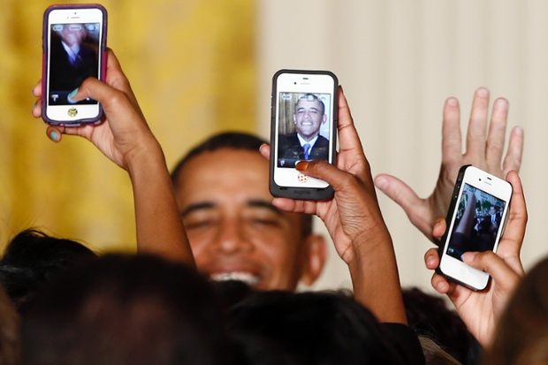 Audience members hold up Apple iPhones to photograph President Barack Obama after he spoke at a Women's History Month reception in the East Room at the White House in Washington.