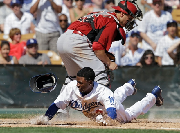 Los Angeles Dodgers' Dee Gordon dives home to score after knocking the ball away from Arizona Diamondbacks catcher Miguel Montero in the fifth inning of an exhibition spring training baseball game in Glendale, Arizona. Gordon scored from first on a double by Carl Crawford.