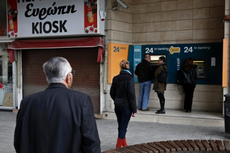 People wait to make transactions at an automated teller machine (ATM) outside a closed branch of the Bank of Cyprus in Nicosia March 19, 2013.