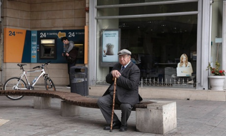 An elderly man sits in front of a closed branch of Bank of Cyprus as a youth makes a transaction at an ATM in Nicosia March 19, 2013.