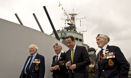 David Cameron walks along the deck of warship HMS Belfast with WWII veterans Lt. Cdr Dick Dykes (left) Jock Dempster (2nd left), and HMS Belfast veteran Frank Bond (right) during a visit to HMS Belfast in London.