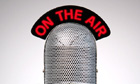 Retro microphone with an On the Air illuminated sign on a desk vignetted