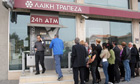Cypriots queue at a Laiki ATM