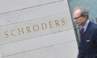 A man walks past a Schroders sign in the City of London