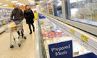 Customers at the frozen prepared meals section at a Tesco store in London