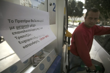 A sign is attached to a petrol pump that explains to clients that they can only pay by cash, in the capital Nicosia, on March 27, 2013.