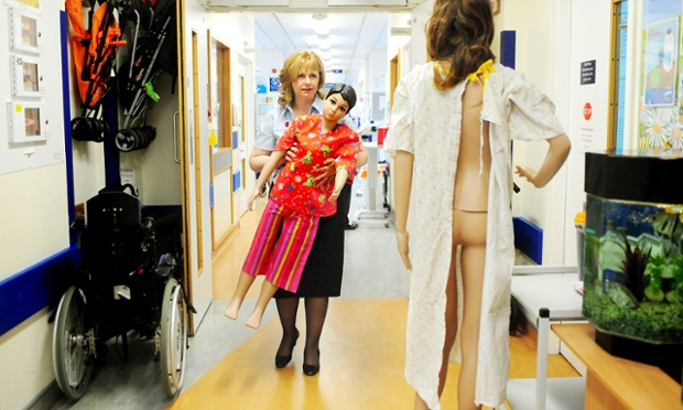 Chief Nurse Michelle McLoughlin carries a mannequin wearing the new two-piece hospital suit for children and younger patients, to replace the old NHS gowns at  Birmingham Children's Hospital, England.