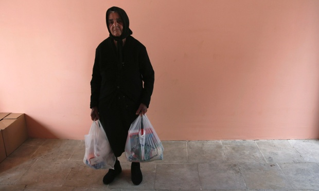Cypriot Andrea Kyriakou, 81, carries bags of food that were given to her by the Orthodox church in Nicosia. Some Cypriots have turned to charity community kitchens for food after banks closed and they were left without cash to buy groceries.