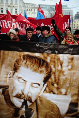 Russian Communist Party leader Gennady Zyuganov walks behind a banner showing an image of Joseph Stalin during a protest in central Moscow against the rising cost of essentials.