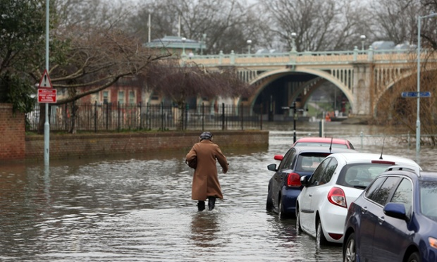 Next up on the weather front. A pedestrian walks down Ranelagh Drive in Richmond which was briefly flooded due to spring tides leaving parked cars under water. Photograph: Steve Parsons/PA