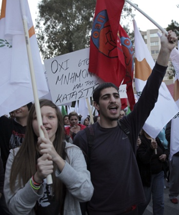 Demonstrators wave flags and banners as they protest outside the European Union House in the Cypriot capital Nicosia on March 27, 2013.