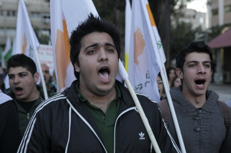 Cypriot demonstrators shout slogans as they hold their national flag during a protest outside the European Union House in the Cypriot capital Nicosia on March 27, 2013.