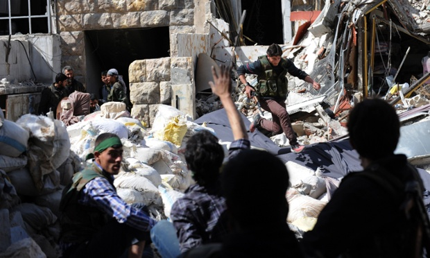 A Syrian opposition fighter runs for cover from Syrian army snipers as they try to cross the rubble during clashes in the northern city of Aleppo.