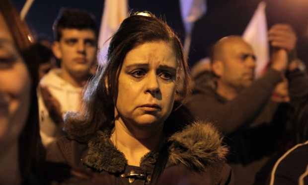 A woman sheds tears during a protest infront of Presidential Palace in Nicosia, Cyprus. A noisy crowd of about 1,500 staged a march through the capital to protest a eurozone bailout deal which delivers a major hit to big bank depositors and will see thousands left jobless.