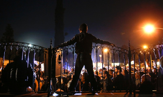 A protester stands atop the fence at the Presidential Palace during an anti-bailout rally in Nicosia March 27, 2013.
