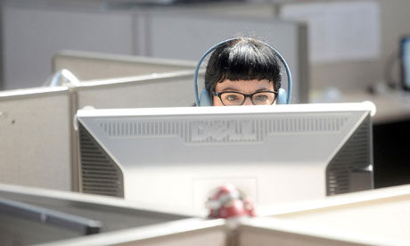 Woman with headphones sat at a computer