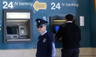 A policeman stands near an ATM outside a branch of Laiki bank in Nicosia, Cyprus