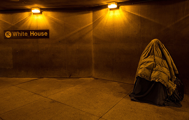 24 hours in pictures: Washington, USA: A homeless person covered in blankets sleeps at the entran