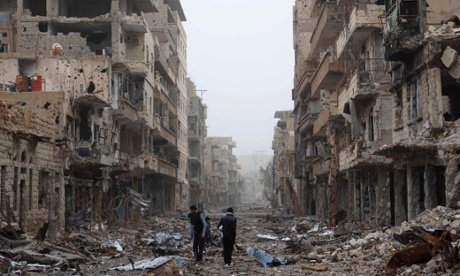 People walk throught damaged areas of Deir al-Zor, Syria.