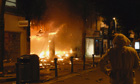 A bystander looks at a blazing store  in Woolwich, southeast London