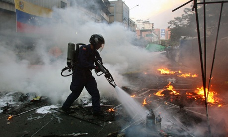 A firefighter extinguishes a fire set by supporters of President Hugo Chavez to burn the belongings of opposition students who had been demanding information on Chavez's health, and fled after hearing of his death.