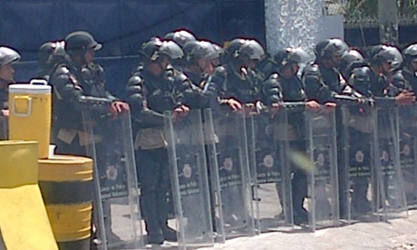 Riot police protect the private TV station Globovision.