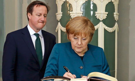 German Chancellor Angela Merkel signs the guestbook at Schloss Meseberg as David Cameron looks on