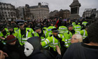 Police officers and protesters scuffle in Trafalgar Square