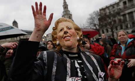 A protester wears a Thatcher mask at a Trafalgar Square party to mark her death