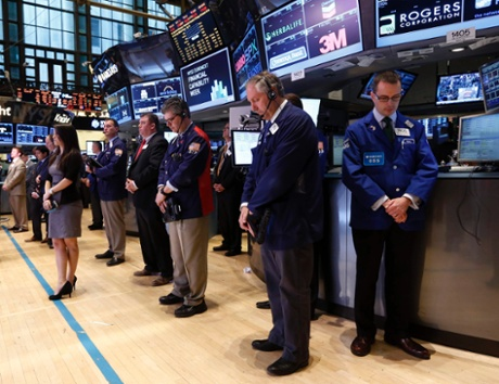 Traders observe a moment of silence to honor the victims and families of the Boston Marathon bombings, before the opening bell on the floor of the New York Stock Exchange, April 16, 2013.
