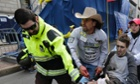 An emergency responder and volunteers, including Carlos Arredondo in the cowboy hat, push Jeff Bauman in a wheel chair after he was injured in an explosion near the finish line of the Boston Marathon Monday, April 15, 2013 in Boston.
