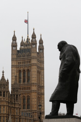 The Union flag flies at half mast above the Houses of Parliament, behind a statue of Winston Churchill, on a grey, drizzly day in London.
