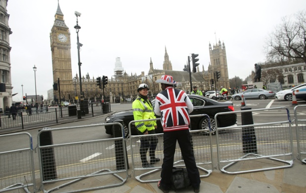 A spectator sporting a Union Flag hat and jacket gets his very own police officer in Parliament Square.