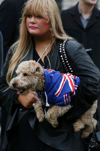 A woman holds her patriotic dog outside the Houses of Parliament.