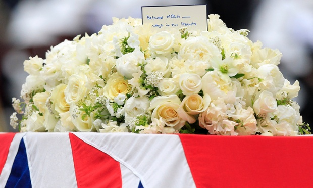 A floral tribute with a card on top of the Union flag draped coffin.