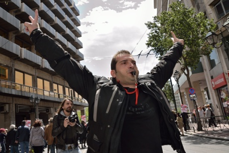 A demonstrator is seen making noise with a whistle.