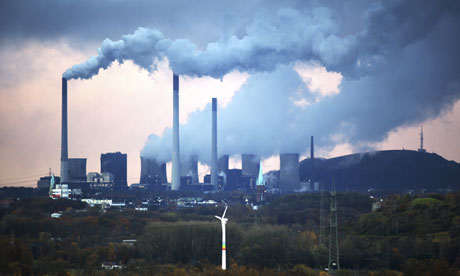 A coal-fired power station in Gelsenkirchen, Germany dwarfs a wind turbine in the foreground.
