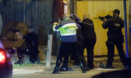 Police officers aim their weapons amid a hunt for two suspects caused officers to converge on a neighborhood outside Boston.
