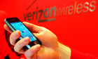Verizon employee holds an iPhone