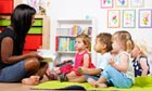 Happy, bright picture of childminder sitting crosslegged reading to four attentive children